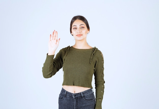Une jeune femme souriante en pull vert agitant la main.