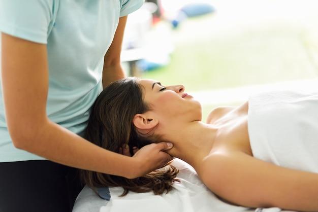 Jeune femme souriante recevant un massage de la tête dans un centre de spa.