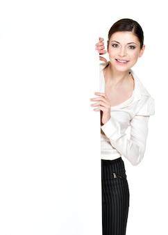 Jeune femme souriante à la recherche d'une bannière vierge blanche - sur l'espace blanc