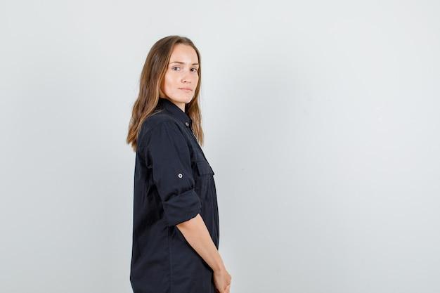Jeune femme souriante et regardant la caméra en chemise noire et à la recherche de confiance.