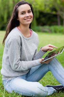 Jeune femme souriante regardant la caméra tout en maintenant son tablet pc