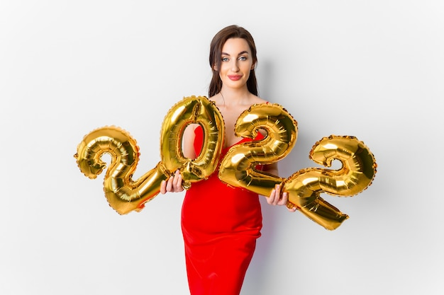Jeune Femme Souriante En Robe De Cocktail Rouge Avec Un Maquillage Lumineux Célébrant Le Nouvel An Et Tenant De L'or... Photo Premium