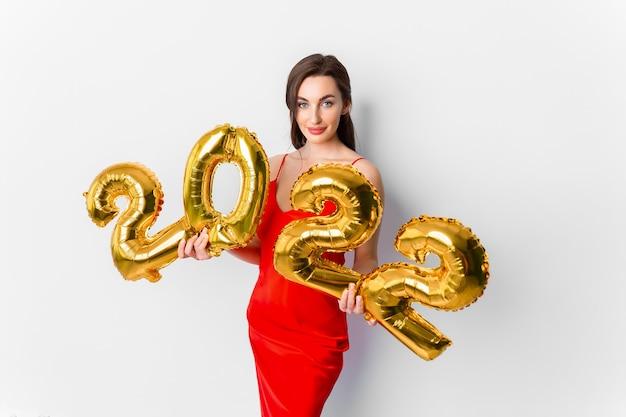 Jeune femme souriante en robe de cocktail rouge avec un maquillage lumineux célébrant le nouvel an et tenant de l'or...