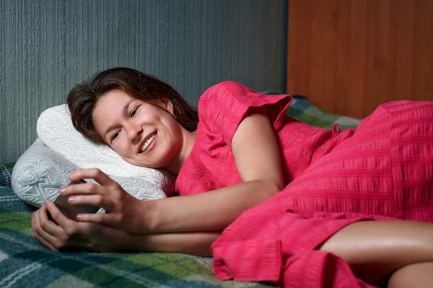 Jeune femme souriante en robe rouge allongée sur le lit et à l'aide de smartphone