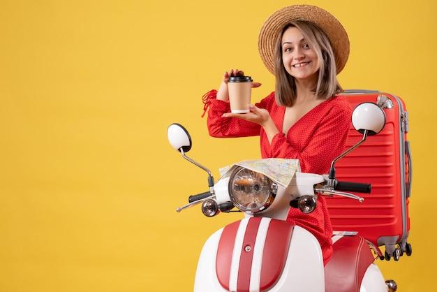 Jeune femme souriante en robe rouge tenant une tasse de café près d'un cyclomoteur