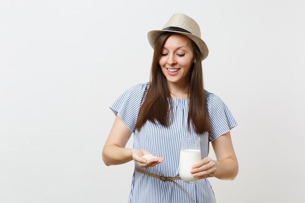 Jeune femme souriante en robe tenir dans les mains lait de riz en verre, poignée de riz isolé sur fond blanc. une bonne nutrition, une boisson végétarienne végétalienne, un concept de régime alimentaire sain. espace de copie.