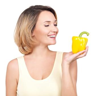 Jeune femme souriante saine tient le poivre isolé sur blanc.