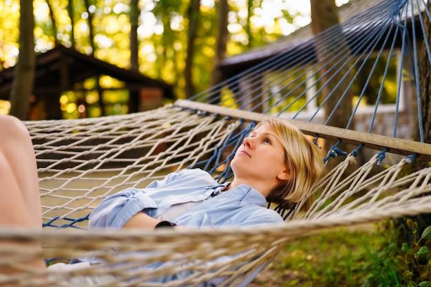 Jeune femme souriante se détendre dans un hamac au jour d'été.