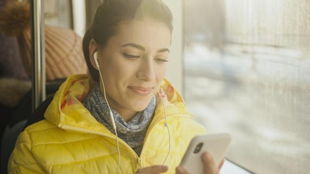 Jeune femme souriante en se tenant debout dans le train, le tramway ou le bus. passagère heureuse, écouter de la musique sur un smartphone dans les transports publics.