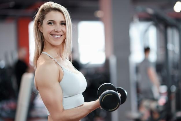 Jeune femme souriante soulevant des haltères dans la salle de gym. concept de musculation féminin