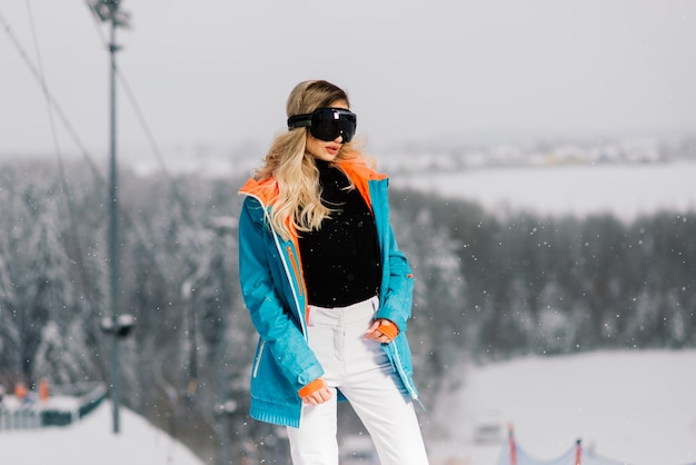 Jeune femme souriante sportive en hiver avec snowboard, lunettes