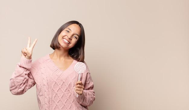 Jeune femme souriante et à la sympathique, montrant le numéro deux ou seconde avec la main en avant, compte à rebours