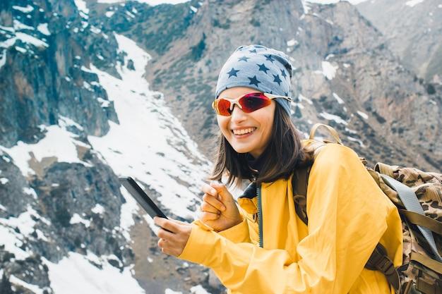Jeune femme souriante tapant un message sur smartphone dans les montagnes enneigées rocheuses