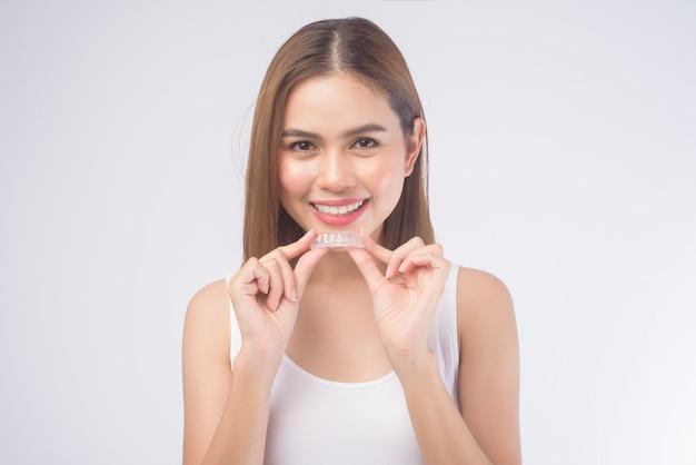 Une jeune femme souriante tenant des accolades invisalign sur blanc