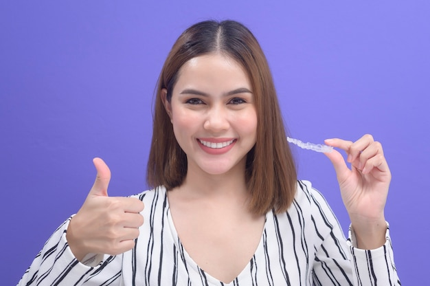 Une jeune femme souriante tenant des accolades invisalign en studio, soins dentaires et concept orthodontique.