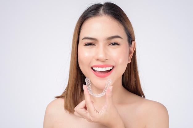 Jeune femme souriante tenant des accolades invisalign en studio, soins dentaires et concept orthodontique
