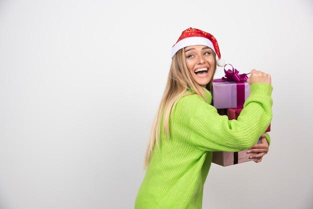 Jeune femme souriante tenant dans les mains des cadeaux de noël festifs