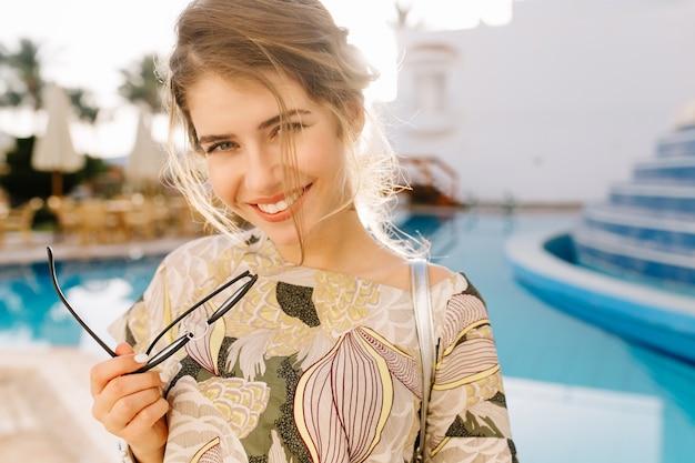 Jeune femme souriante, tenant des lunettes à la main. belle piscine, hôtel spa, complexe. avoir du bon temps, profiter des vacances, des vacances. porter un t-shirt élégant, une manucure courte.