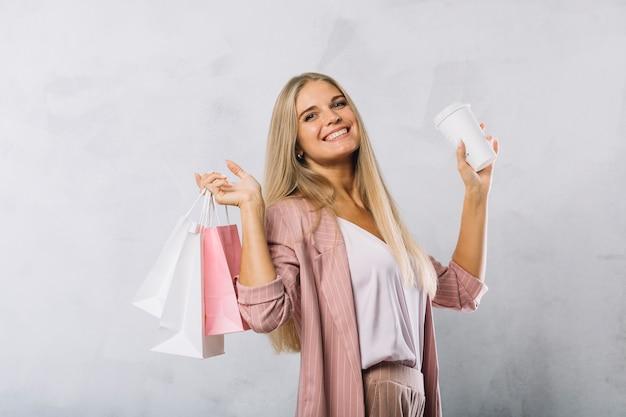 Jeune femme souriante tenant des sacs à provisions