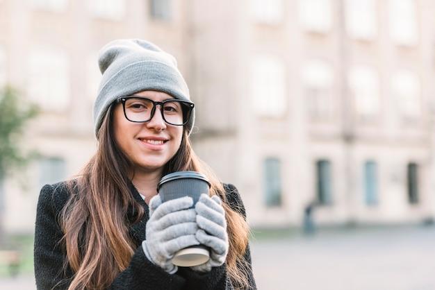 Jeune femme souriante tenant une tasse de boisson dans la rue