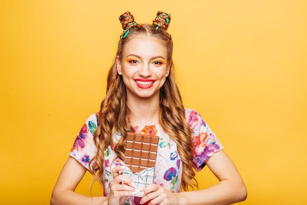 Jeune femme souriante tient la barre de chocolat