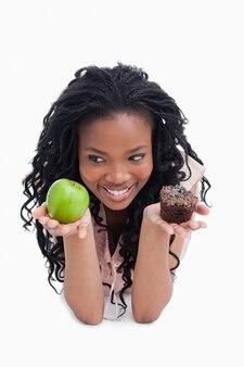 Une jeune femme souriante tient une pomme et un petit pain sur la paume de ses mains