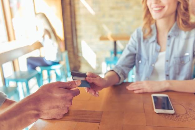 Jeune femme souriante tout en donnant une carte de crédit.