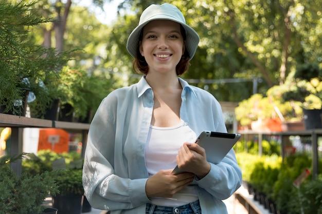 Jeune femme souriante travaillant dans une serre
