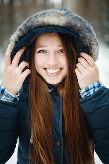 Jeune femme souriante en vêtements d'hiver avec capuche debout dans la forêt d'hiver, riant, regardant la caméra. paysage d'hiver sur le fond.