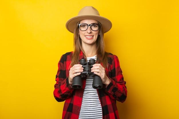 Jeune femme avec un sourire dans un chapeau et une chemise à carreaux tenant des jumelles dans ses mains sur un fond jaune.