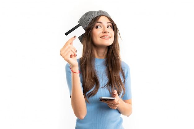 Jeune femme avec un sourire délicieux, de longs cheveux châtains ondulés, un beau maquillage, en jersey bleu, un jean noir, un béret gris, debout avec téléphone et carte