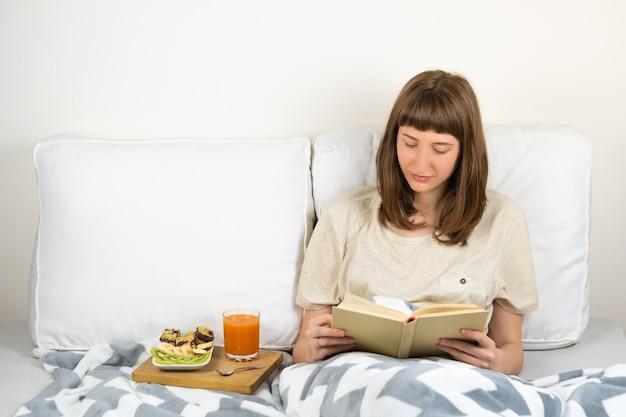 Jeune femme sourit et lit un livre au lit et prend le petit déjeuner