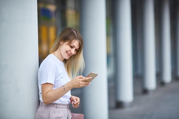 Jeune femme sourit et tient dans ses mains et regarde le smartphone. copiez l'espace.