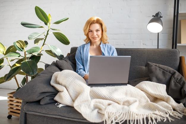 Jeune femme, sous, a, couverture, utilisation, ordinateur portable, sur, divan
