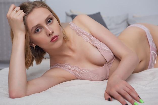 Jeune femme en sous-vêtements au lit