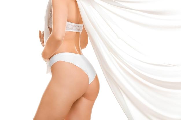 Jeune femme en sous-vêtements sur blanc. concept de chirurgie plastique
