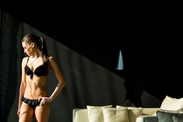 Jeune femme en sous-vêtements dans la chambre