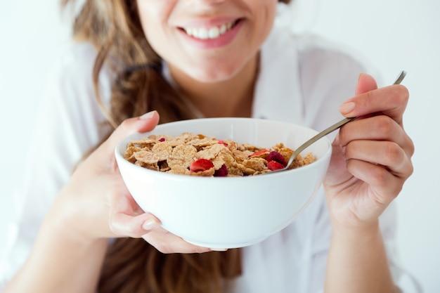 Jeune femme en sous-vêtements, manger des céréales. isolé sur blanc