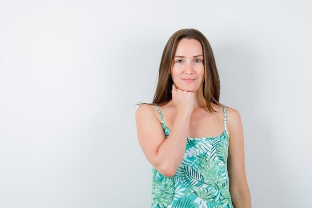 Jeune femme soutenant le menton sur le poing en chemisier et magnifique, vue de face.