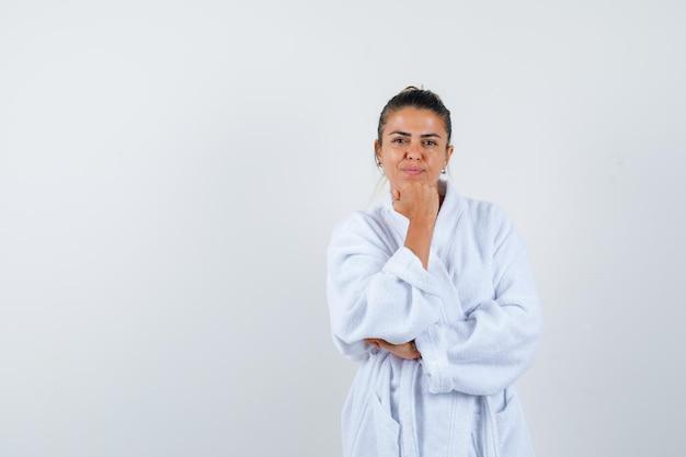 Jeune femme soutenant le menton sur le poing en peignoir et ayant l'air confiant