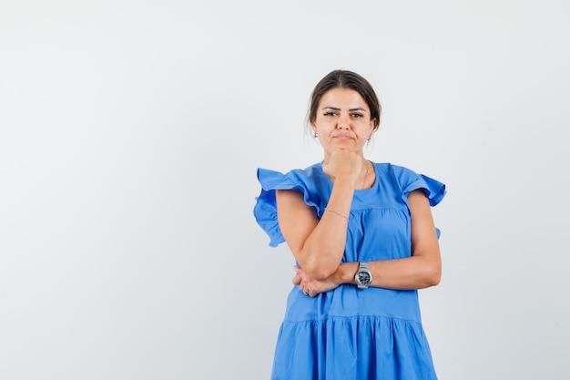 Jeune femme soutenant le menton sur le poing en robe bleue et ayant l'air sensible