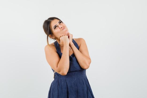 Jeune femme soutenant le menton sur les poings en robe et semblant rêveuse