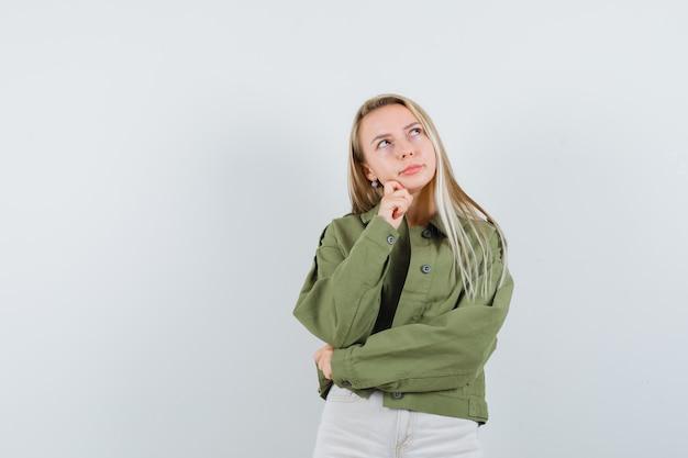 Jeune femme soutenant le menton à portée de main dans la veste, le pantalon et l'air rêveur. vue de face.