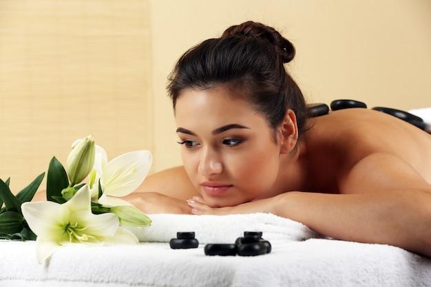 Jeune femme, à, spa, pierres, sur, elle, dos, sur, table massage, dans, beauté, spa, salon
