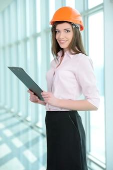 Jeune femme spécialiste de la construction examinant des plans.