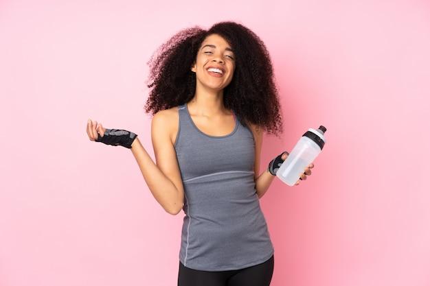 Jeune femme de sport afro-américaine sur mur rose avec bouteille d'eau de sport