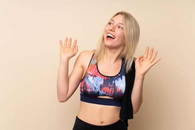 Jeune femme sport blonde sur un mur isolé avec une expression faciale surprise