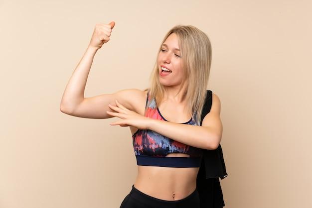 Jeune femme de sport blonde sur mur isolé faisant un geste fort