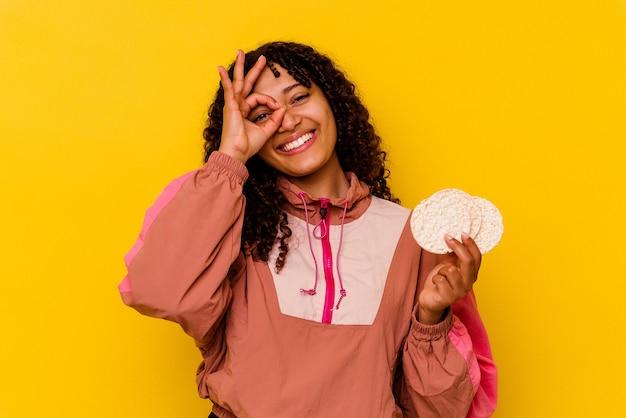 Jeune femme de sport métisse tenant un gâteaux de riz isolé sur fond jaune excité en gardant le geste ok sur les yeux.
