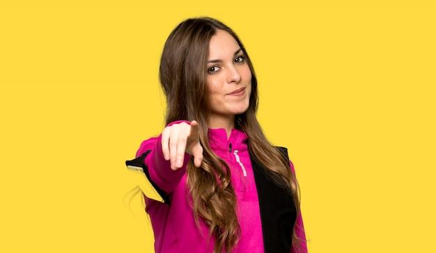 Jeune femme sport pointe le doigt vers vous avec une expression confiante sur fond jaune isolé
